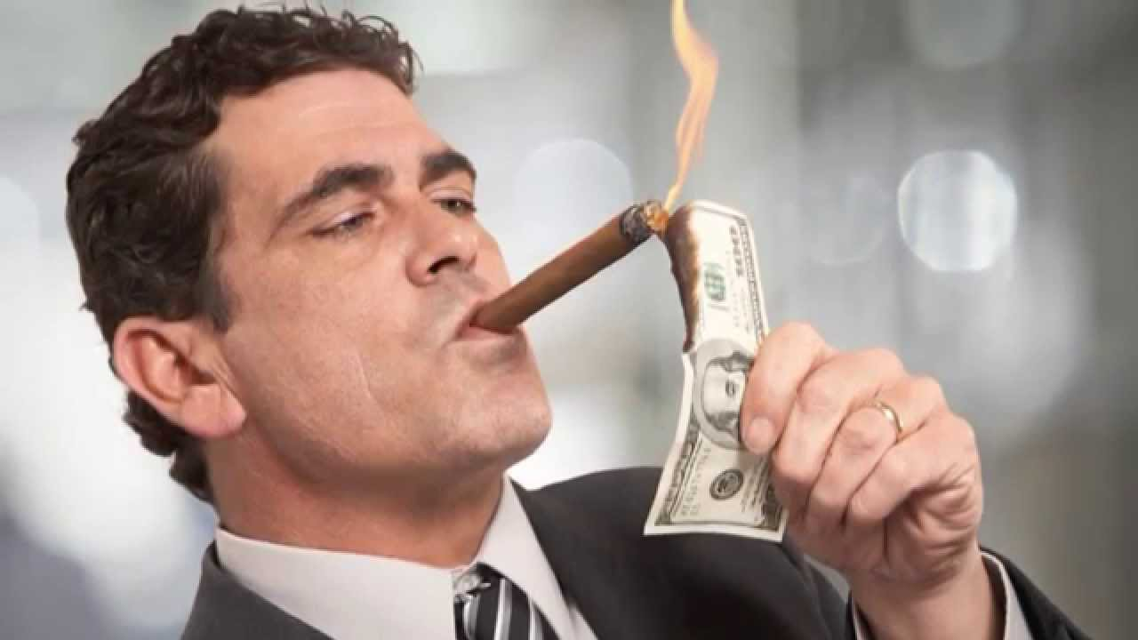 Man smoking a cigar from a hundred dollar bill.