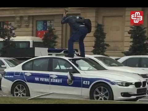 Sürücü polis maşınını çəkiclə əzir