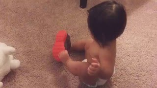 Baby tries to put on shoes