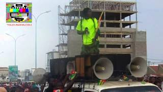 L'artiste engagé Amen Jah Cisse anime la marche dans la foule et debout sur un bus