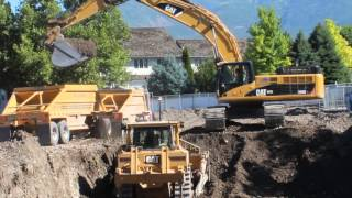 CAT D8T Bulldozer drives into hole to help 345D Excavator load a double big rig dump truck