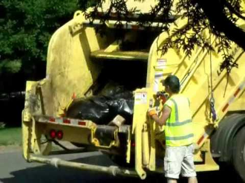 Yellow Rear Loader Garbage Truck Packing...