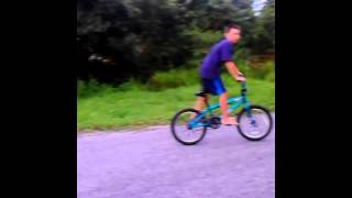 Kid popping wheelie on bike