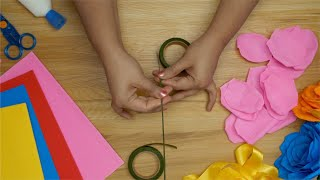 Girl making the stem of an artificial pink rose using tape