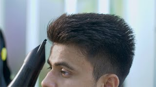 Closeup shot of a barber blow drying hair after the haircut