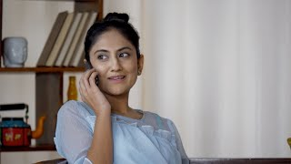 Attractive Indian female having a friendly mobile phone conversation sitting at home