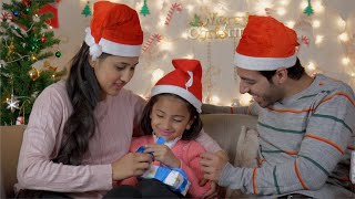 Happy Indian family with daughter wrapping Christmas gift while sitting on a couch