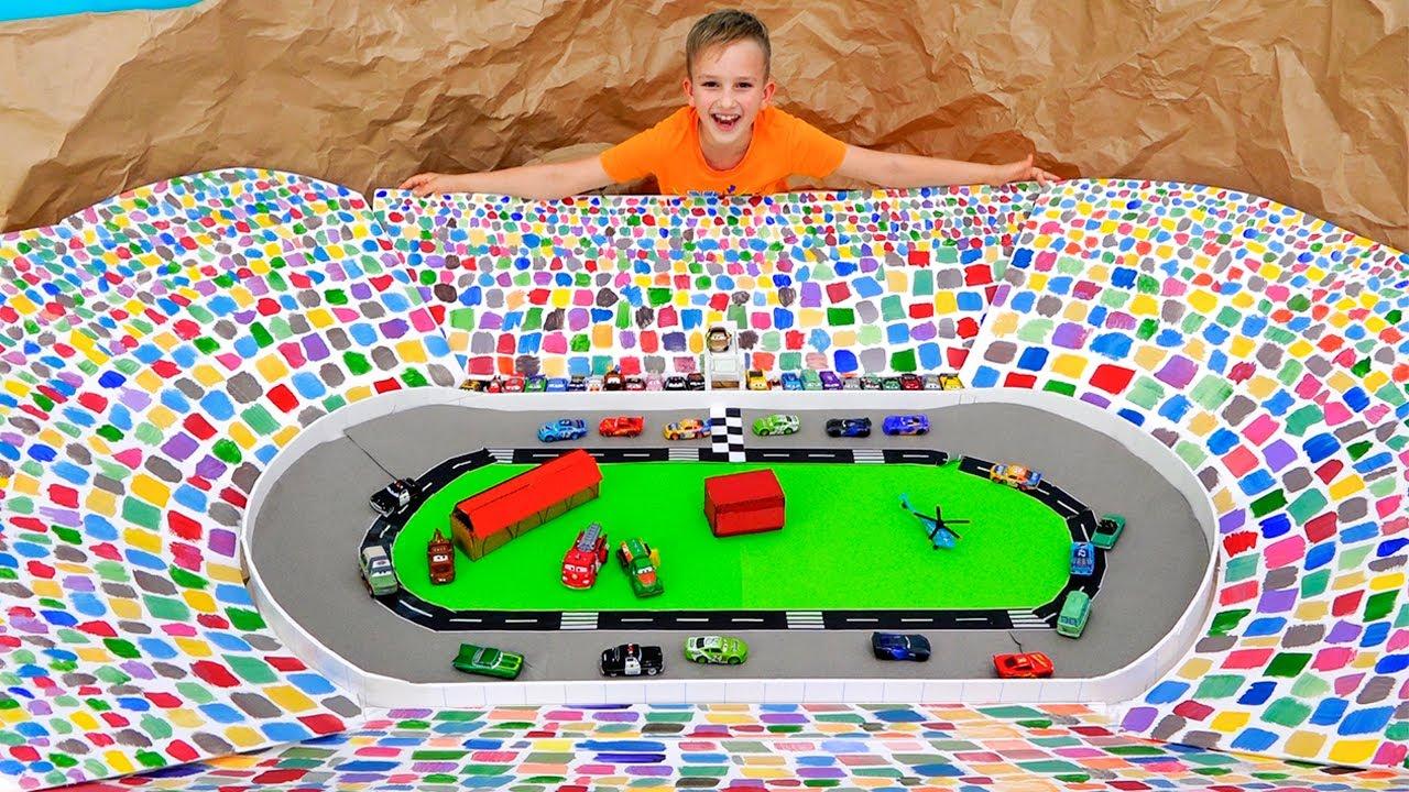 Vlad et Niki jouent avec des voitures miniatures et construisent une piste de Speedway