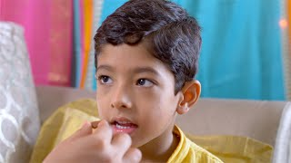 A cute little boy enjoys a piece of chocolate on raksha bandhan