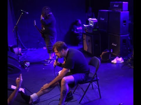 NAPALM DEATH's vocalist performs in a chair due to ankle injury full concert posted!