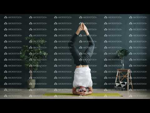 slow-motion-of-advanced-yoga-student-doing-headstand-working-out-in-studio