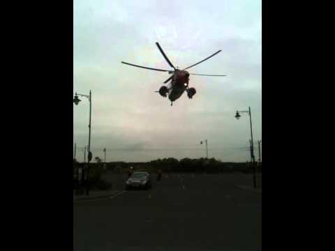 Irish coastguard rescue helicopter at Malahide winching up casualty from marina car park