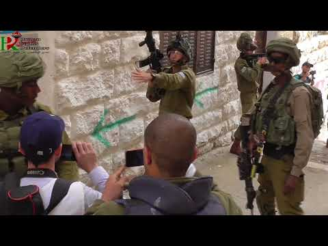 The occupation army is breaking the entrance of a Palestinian house in Hebron