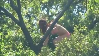 Девушка прыгает с дерева в воду. Парк