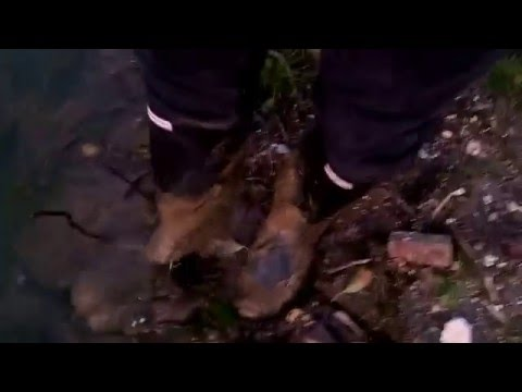 Cleaning muddy black Hunter wellies in pond