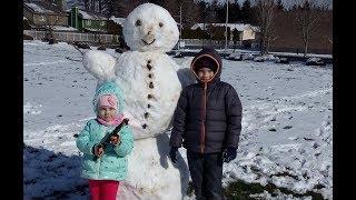 Настя и Никита лепят снеговика. Дети играют в снежки и смеются.