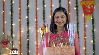 Pretty Indian female smiling with a box of firecrackers in traditional clothing