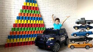 Машинки Форд сбивают гигантские пирамиды из цветных стаканчиков.