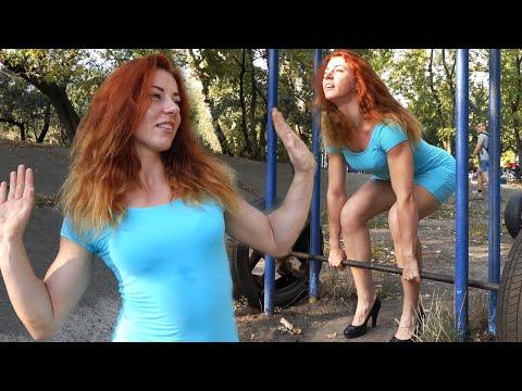 Девушка тренируется на турниках в вечернем платье и на высоких каблуках.