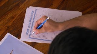 Close-up of young corporate executive filling Home Loan Application form on a paper sheet