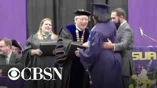 Woman in labor walks across graduation stage to receive college diploma