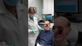 9/11 responder receives his prosthetic left upper jaw with teeth and his prosthetic face.