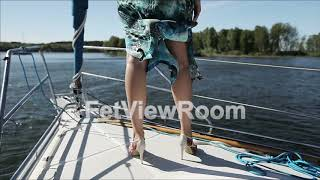 Slender legs of a young girl in high heels on a yacht