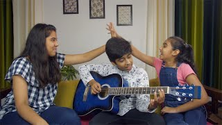 Happy siblings enjoying singing while playing guitar - spending family time together