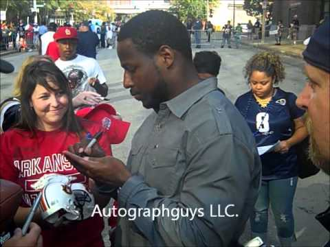 CADILLAC WILLIAMS OF THE ST. LOUIS RAMS SIGNING AUTOGRAPHS AFTER A RECENT RAMS HOME GAME