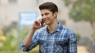 Young happy man talking to a friend on phone outside in a park