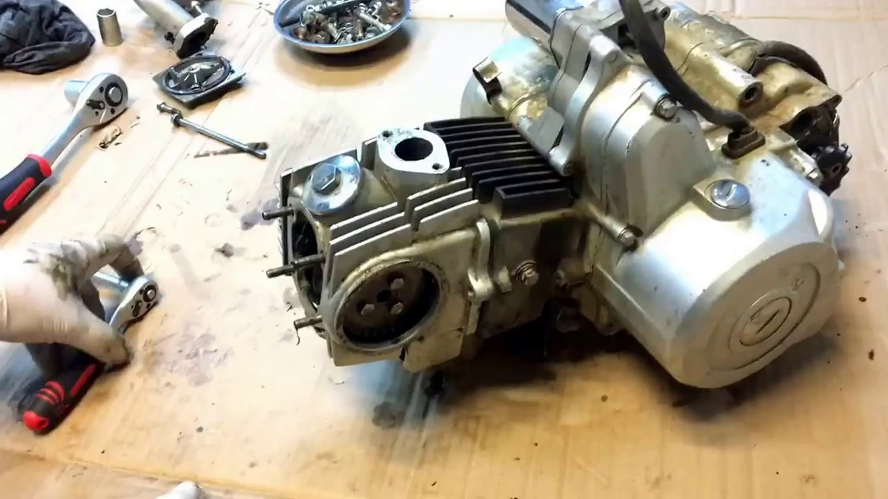 Disassembled engine and cylinder head on ATV 107 110 125 cc