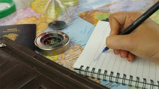 "Closeup shot of woman hands writing a word ""travel"" in a diary - travel concept"