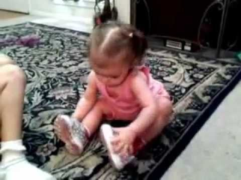Big Brother helps little sister put shoes on.