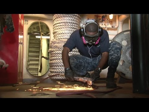 Seaman Apprentice Grinds The Deck Of Aircraft Carrier USS George H.W. Bush