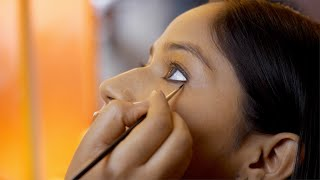Closeup view of an Indian makeup artist applying kajal to a model - makeup concept