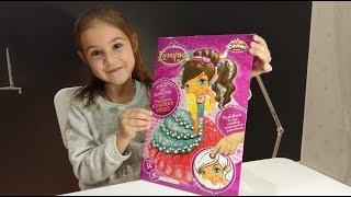 Лера раскрашивает куколку пластилином и блестками. Набор для творчества.