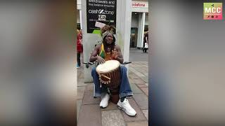 African busker laughs while playing jambe in Glasgow
