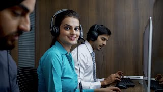 Young beautiful woman attending a call and resolving customer query - Call center employee