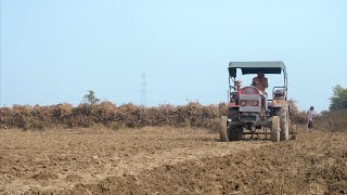 Indian farmer plowing the field with the help of tractor - Modern way of agriculture