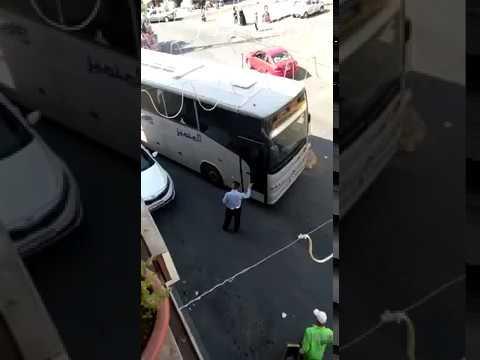 Wide bus in narrow street closed by a car in Jordan