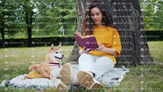 Pretty curly-haired girl student reading book sitting in park on lawn with dog