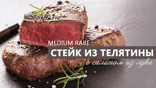 Стейк medium rare из телятины на сковороде с салатом из лука.