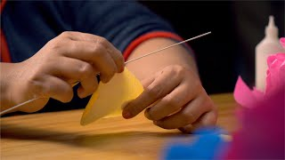 A clip of paper craft where a flower petal is being crafted