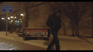 A very drunk man walking down the street on a very cold night