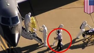 Ebola risk: Man without hazmat suits helps patient onto CDC plane: 'Clipboard Man' enrages Twitter
