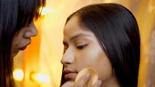 An Indian makeup artist busy applying foundation to her client - makeup in the process