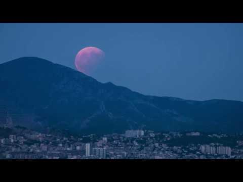 La pleine lune partiellement éclipsée se lève sur Marseille