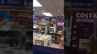Drunk Asian man working in a petrol station
