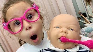 Valentina fingir brincar com bebê de brinquedo de escovar os dentes