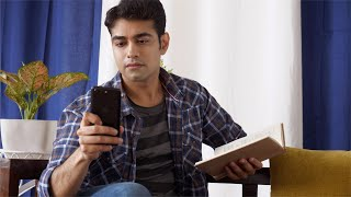 Young Indian man reading a book and attending an urgent call
